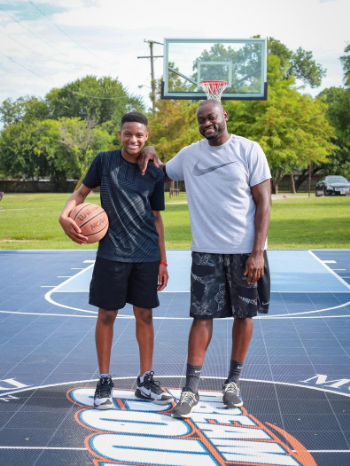 Father and son smiling, standing on basketball court with ball