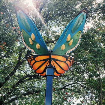 Butterfly sculpture with wings painted with larva and butterflies