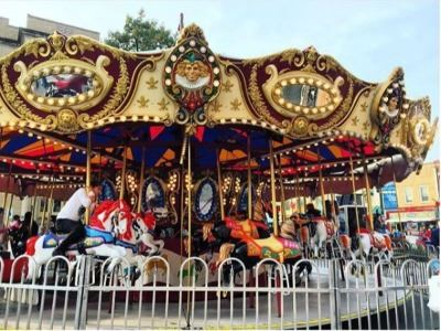 Large decorated carousel with horses and children
