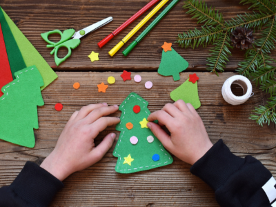 Child's hands holding a felt Christmas Tree ornament surrounded by craft supplies Opens in new window
