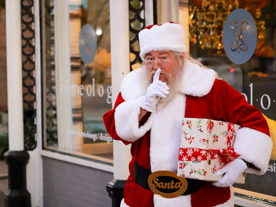 Santa in front of a store holding a wrapped package with his finger to his lips