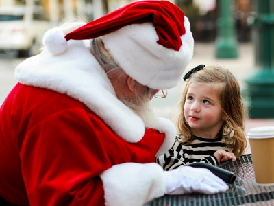 Santa and a little girl sitting at a table talking