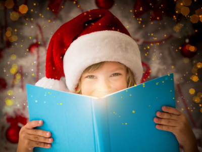 Little Girl in a Santa hat holding a book.