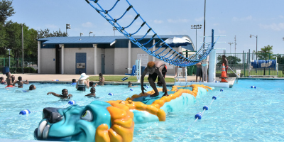 A child running across the floating dragon bridge at Juanita Maxfield Aquatic Center.