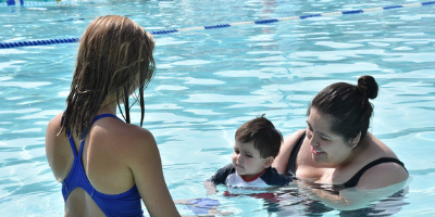 A parent holding a small child. The Swim Instructor is holding a toy out to them.